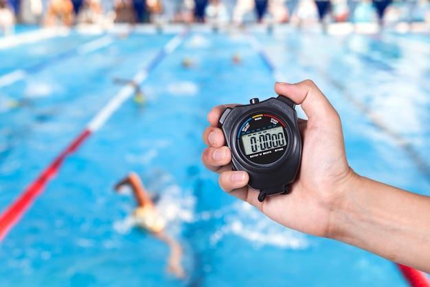 ストップウォッチは、水泳の背景の競争と手を保持します。