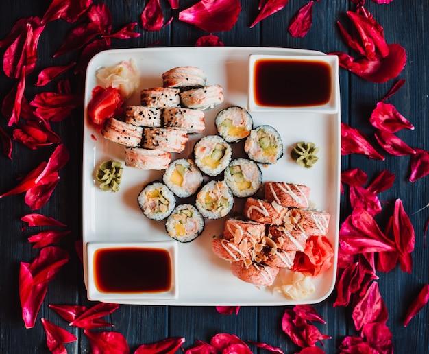 Набор суши с васаби, соевым соусом на черном фоне