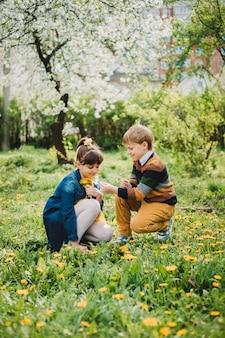 Девочка и мальчик, держа в руках одуванчик