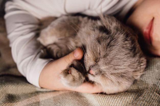 Кошка и мальчик спят вместе обнялись