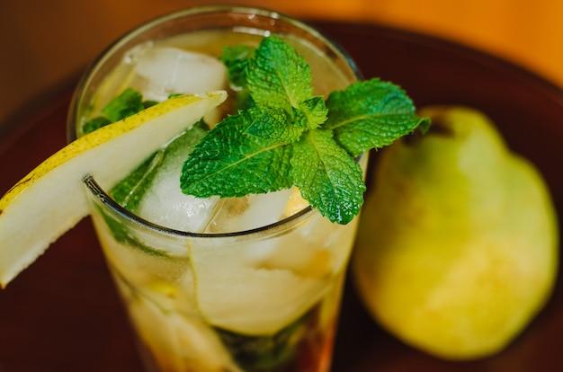 Свежий холодный лимонад с грушей, лимоном и мятой на деревянный стол.