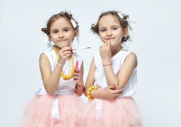 母親の化粧で遊ぶ二人の少女