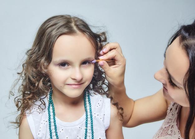 彼女の小さな娘の化粧をしている母親