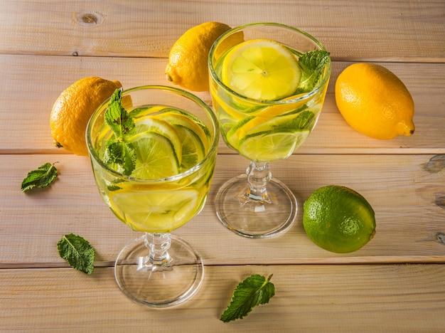 Летний освежающий коктейль мохито с лаймом и мятой на деревянный стол.