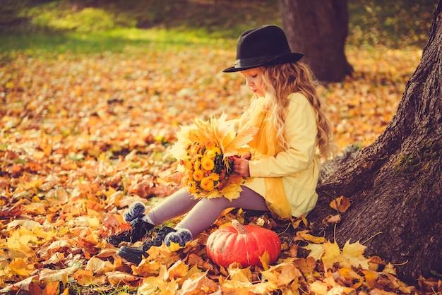 秋の公園で大きなカボチャとブロンドの髪を持つ美しい少女。