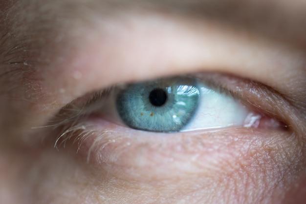 Голубые глаза мужчины крупным планом макро фон