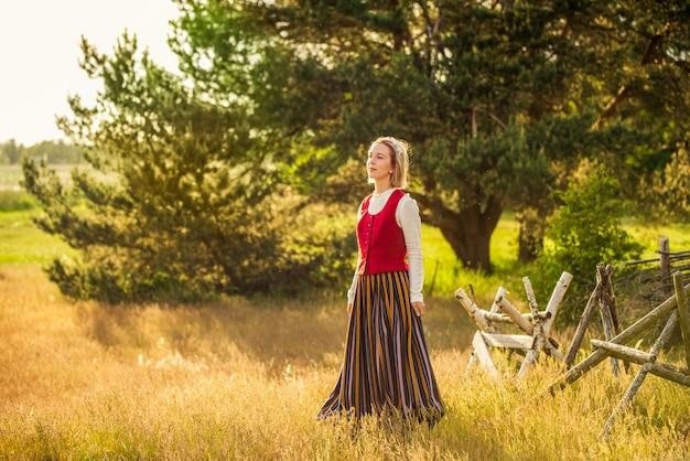 Латышка в традиционной одежде в поле