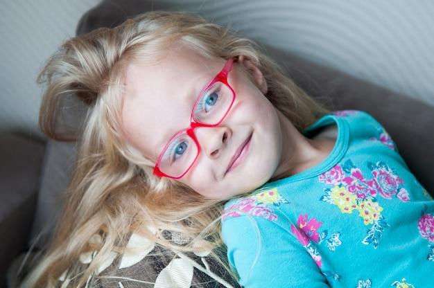 Милая маленькая белокурая девушка с красными стеклами в софе дома