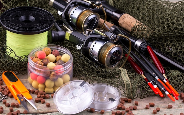 釣り竿とスピニング、テーブルの古い表面で釣りをするためのアクセサリー付きのコンポジション