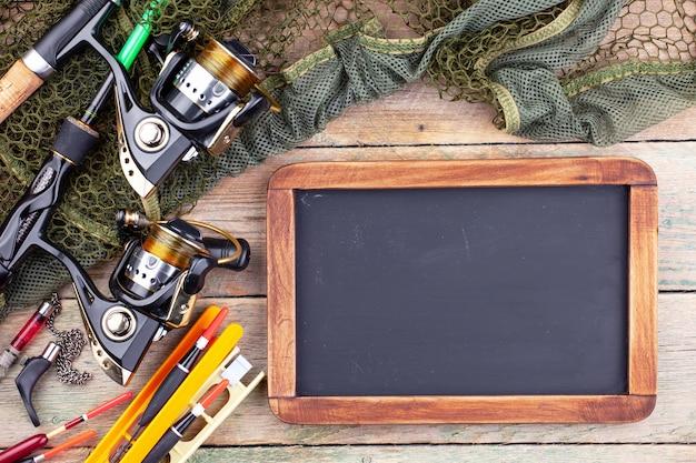 釣り竿、黒板、テーブルの古い表面での釣り用アクセサリーと組成のスピニング