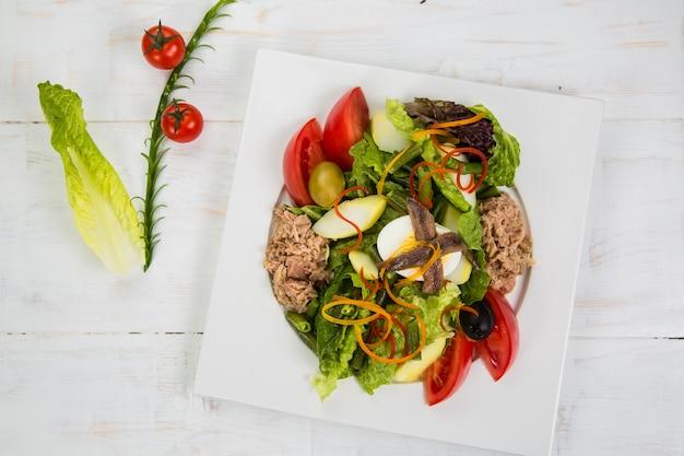 Тунец, анчоусы, яйца. зеленое блюдо, кусочки сладкого желтого перца, красный лук, черные оливки и помидоры вкусный салат на белой тарелке