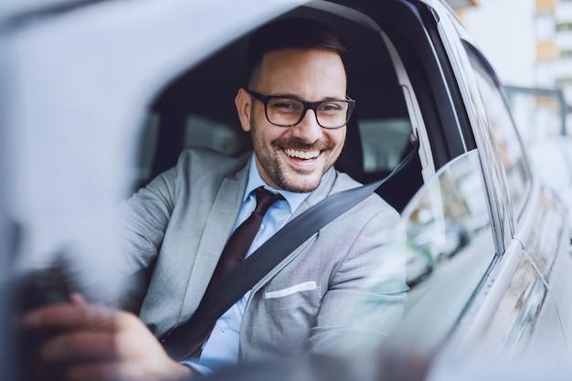 陽気な白人ビジネスマンが仕事に自分を運転します。手がハンドルにあります。