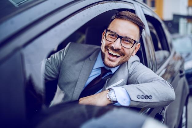 彼の高価な車を運転している間トラフウィンドウを探しているビジネスマンの笑みを浮かべてください。出張のコンセプトです。