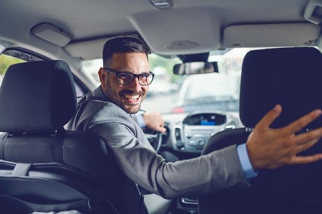 陽気な白人実業家が彼自身を運転する運転の後姿。手がハンドルにあります。