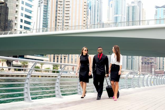 Три человека, идущие на встречу, идут по улице, обсуждают планы