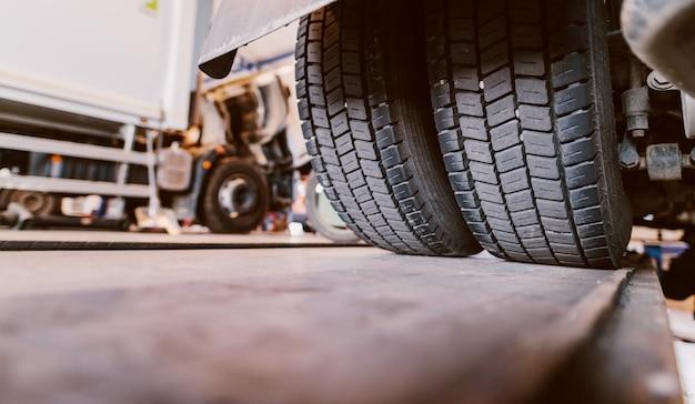 トラックのタイヤのクローズアップ。車のワークショップで古いトラックを修復します。