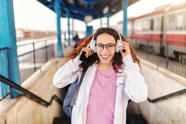 Красивый девочка-подросток при зубастая улыбка кладя на наушники пока стоящ на вокзале. в руке смартфон.