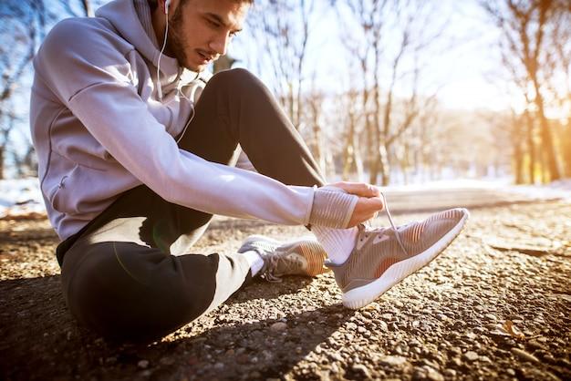 地面に座っている間冬の森で靴ひもを結ぶハンサムな若い男。