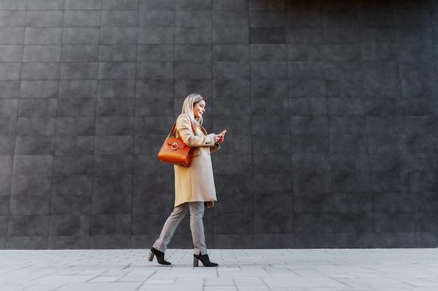Взгляд со стороны привлекательной кавказской белокурой женщины в пальто проходя серой стеной снаружи и используя умный телефон.