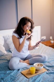 ビスケットを食べながら寝る前にベッドの上に座ってテーブルを見ているかなり満足している中年女性。