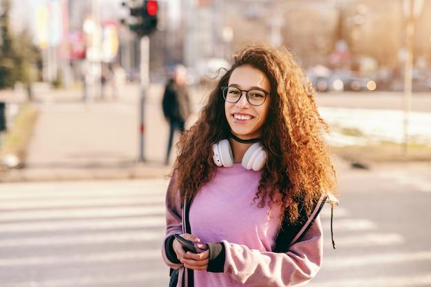 美しい若い流行に敏感な混血少女通りに立って、スマートフォンを押しながら探して