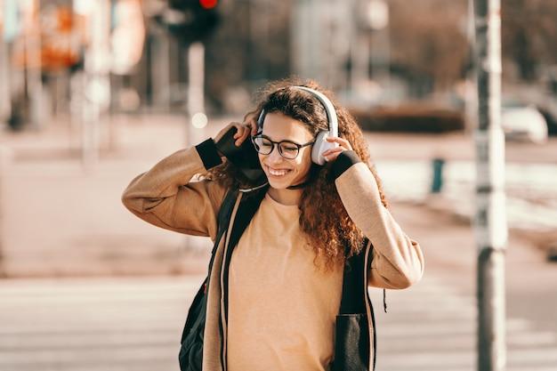 Усмехаясь милая девочка-подросток битника смешанной гонки пересекая улицу и надевая наушники.
