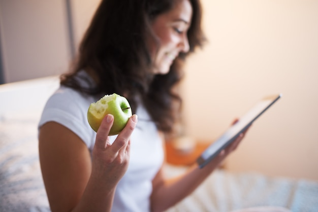 ベッドの上に座って、タブレットを見ながらリンゴを押しながら笑顔の美しい中年の女性のクローズアップ。手とかじったリンゴ。
