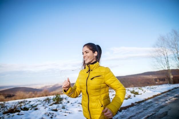 雪に覆われた自然の中で実行している間楽しい時を過す黄色のジャケットでゴージャスな若い女の子。