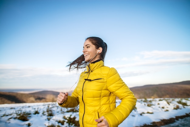 雪に覆われた自然の中で実行されている冬のスポーツウェアでふわふわポニーテールで若い満足満足のやる気と集中のスポーティなアクティブな女の子の側面図です。