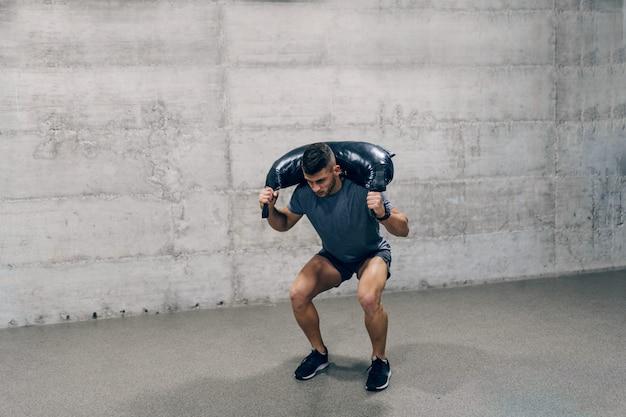 Сильный кавказский спортивный человек в спортивной одежде, лифтинг болгарский тренировочный мешок.