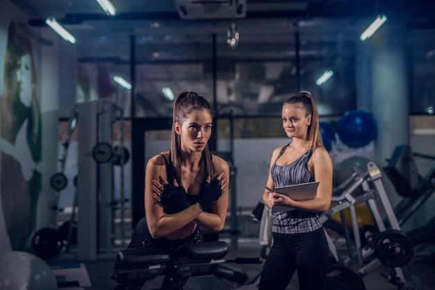 Тренировки подходящей девушки детенышей работая в спортзале пока ее личный тренер в наблюдать ее.