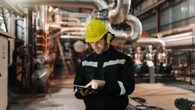 ヘルメットと重工業プラントで、仕事にタブレットを使用して制服を着た白人労働者。