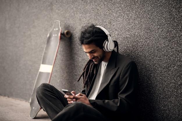 灰色の壁に寄りかかって座っているヘッドフォンでスタイリッシュな若いドレッドロックヒップスターと携帯電話で見ている彼の近くでスケート。