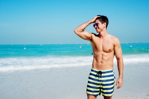 Красивый без рубашки мышечной фитнес человек на пляже, глядя в сторону и улыбается.