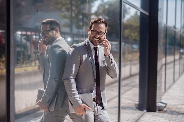 Портрет усмехаясь бизнесмена используя умный телефон пока полагающся на окне. в другой руке планшет.