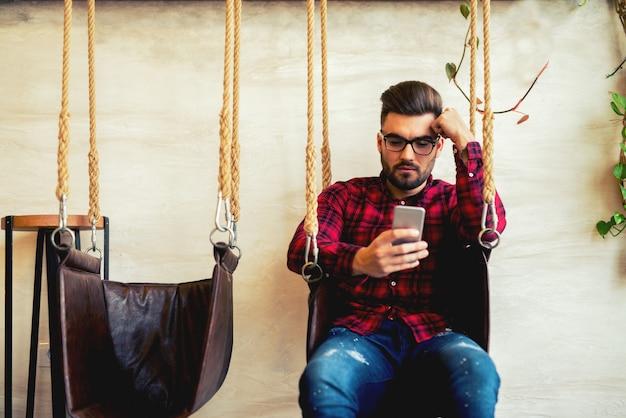 ハンサムな男が誰かにテキストメッセージを送って、ブランコに座っています。