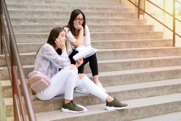 Две веселые молодые школьницы сидят на школьных лестницах с книгами в руках. смеяться и делать домашнее задание.