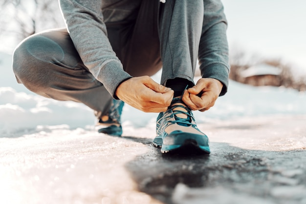 Закройте вверх человека связывая шнурок пока заискивающ. зимний фитнес-концепция.
