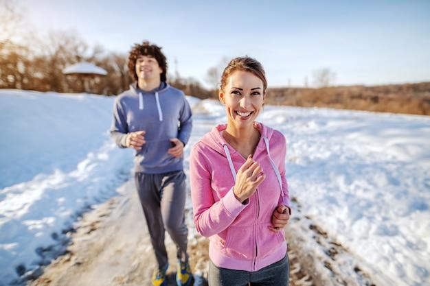自然の中で実行しているスポーツウェアの美しい白人ブルネット。バックグラウンドで彼女の友人は彼女に追いつくことを試みています。冬。