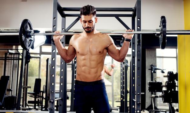 若い筋肉男はジムでバーベルをスクワットします。