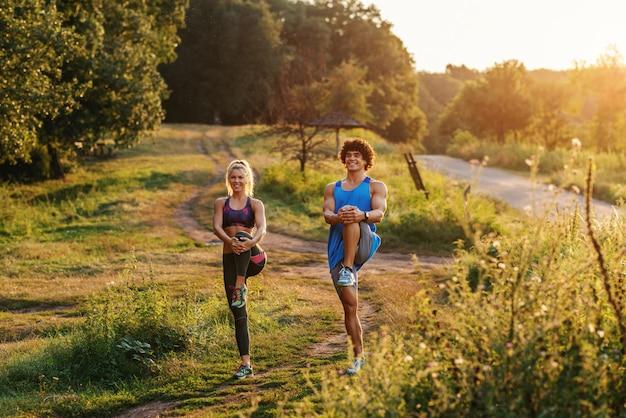 Во всю длину пары стоя на одной ноге и протягивая ноги в природе. солнечный летний день.