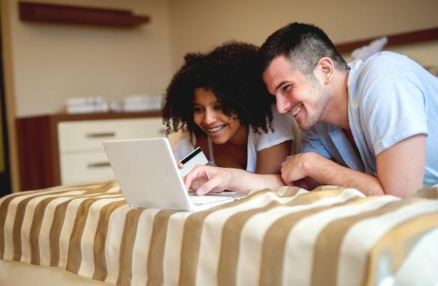家でのんびり、ノートパソコンを見ているカップル。