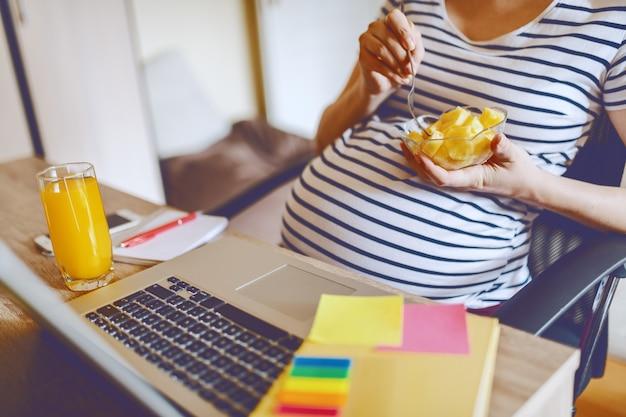 Молодой кавказский беременный фрилансер есть фрукты и сидя дома офис. на столе ноутбук, стакан со свежим апельсиновым соком и блокноты. рабочая концепция беременных женщин.