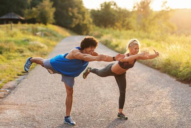 Спортивная пара делает баланс упражнения на одной ноге на дороге в природе. полная длина, солнечный летний день.