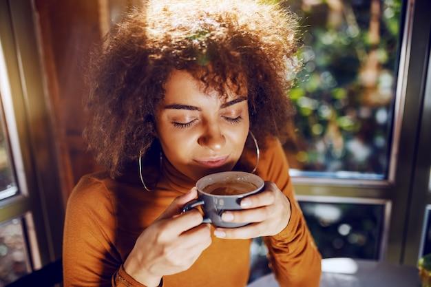 Портрет красивой молодой женщины смешанной расы с вьющимися волосами, сидя в столовой и наслаждаясь кофе.
