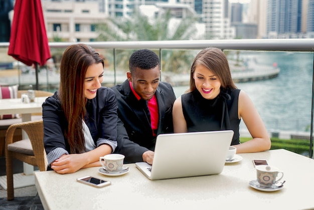 Афро американец и две кавказские дамы работают на ноутбуке возле офиса у реки.