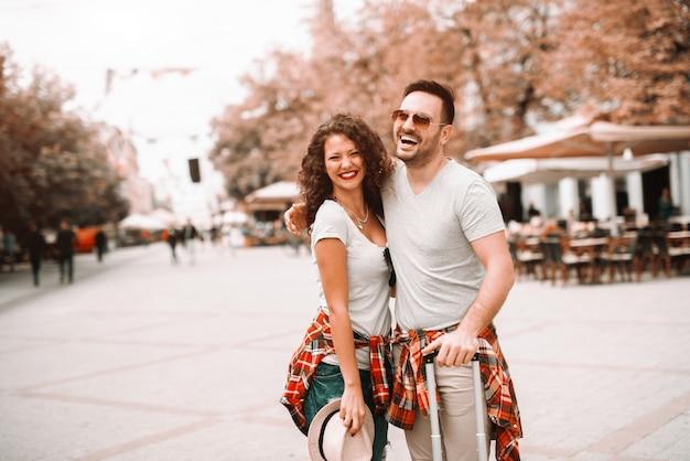 Счастливая пара кавказских стоя на улице и позирует с шляпу и багаж в руках. концепция путешествия.