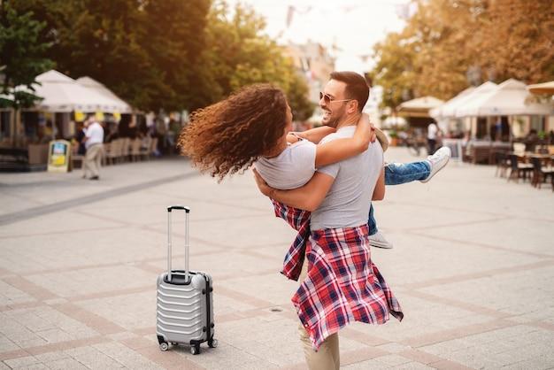 Мужчина держит женщину в руках, стоя на проспекте. путешествия и романтика концепции.