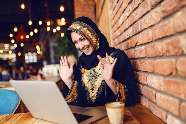 カフェテリアに座ってコーヒーを飲みながらノートパソコンを介してビデオ通話を持つ伝統的な摩耗でゴージャスなイスラム教徒の女性。