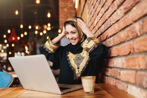 Шикарная мусульманская женщина с зубастой улыбкой одела в традиционной одежде используя компьтер-книжку для он-лайн покупок пока сидящ в столовой. на столе кофе.